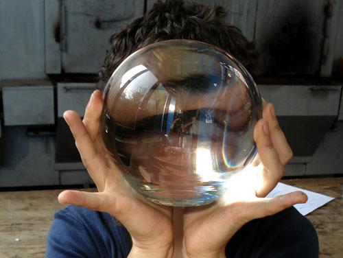 Bola de vidrio maciza. Se ve un ojo ampliado a través de ella.