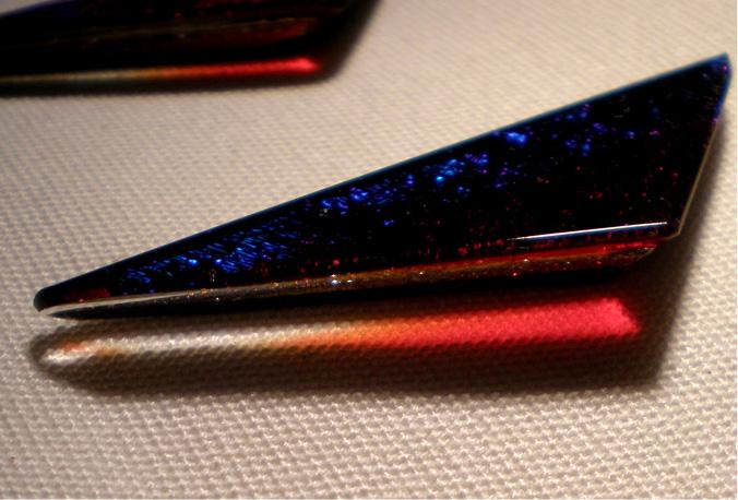 Triángulo de vidrio rojo. Reflejo en la mesa