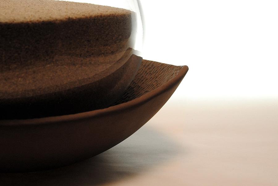 Urna furneraria para ceniza en vidrio soplado incoloro, cierre en madera y bandeja en barro negro esculpito.