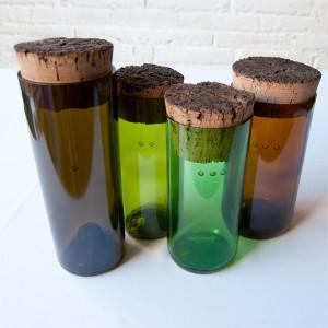 Botellas de vidrio cortadas y reutilizadas como contenedor gracias a un tapón de corcho natural del mismo diámetro que el cuerpo de la botella.